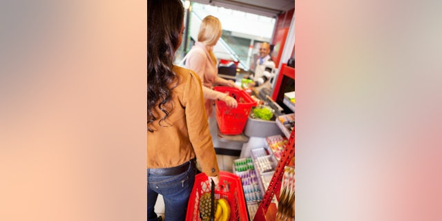 Customers carrying basket while shopping in supermarket