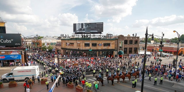 Protesters arrive at Wrigley Field to demand more government action against gun violence, Thursday, Aug. 2, 2018, in Chicago.