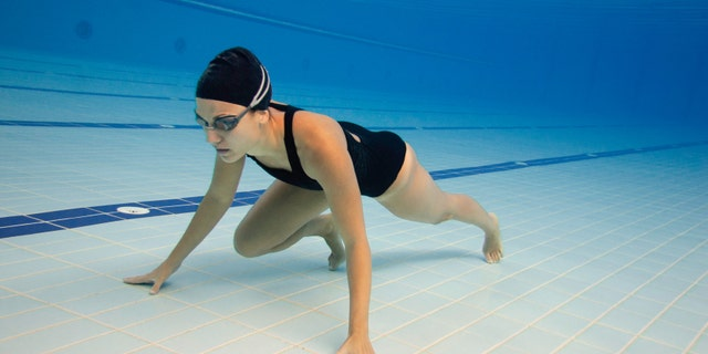 Underwater sprinter in a swimming pool lane. Wide angle, polarization filter, post processed, fine grain added