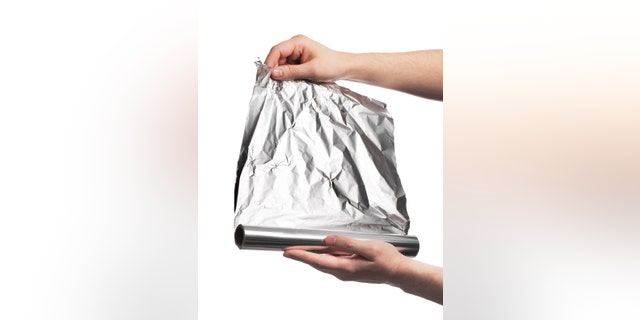 Man holding a roll of household aluminum foil