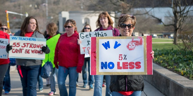 Elizabeth Ferguson Hollifield, a teacher from Princeton W.Va., holds a sign as she walks to a teacher rally Monday, March 5, 2018, at the West Virginia Capitol in Charleston, W.Va.