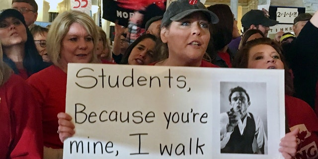 Jennifer Hanner, a first-year teacher from Harts, W.Va., center, holds a sign Thursday, Feb. 22, 2018, outside the state Senate chambers at the Capitol in Charleston, W.Va.