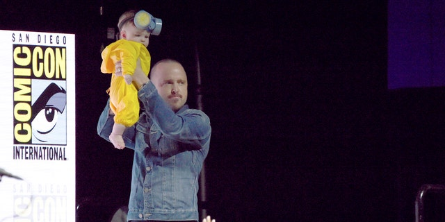 Paul holds his baby daughter over the Comic-Con crowd while dressed in her Walter White costume.