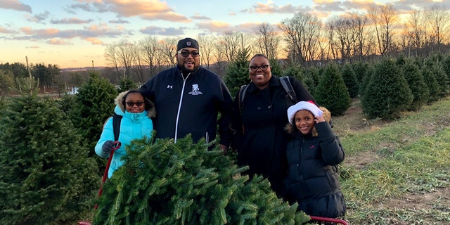 A family cuts down their own tree as part of the Wounded Warrior Project holiday event at the Pine Tree Barn in Wooster, Ohio.