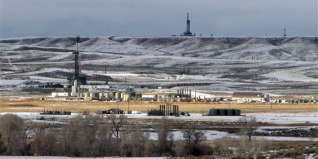 In this Jan. 22, 2010 photo, antelope graze not far from gas drilling rigs in western Wyoming's Upper Green River Basin, where ozone levels last week exceeded the worst days in major U.S. cities last year. (AP Photo/Mead Gruver)