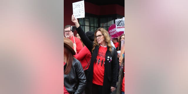 """Elizabeth Perkins joined a Me Too protest and held up a sign that said, """"James Woods #MeToo."""""""