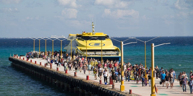 Tourists and passengers disembark from a ferry on to the wharf on Playa del Carmen, Mexico, Friday, March 2, 2018. Undetonated explosives were found on another ferry that runs between the Caribbean resorts of Playa del Carmen and the island of Cozumel, authorities said, less than two weeks after a blast shook another ferry plying the same route.