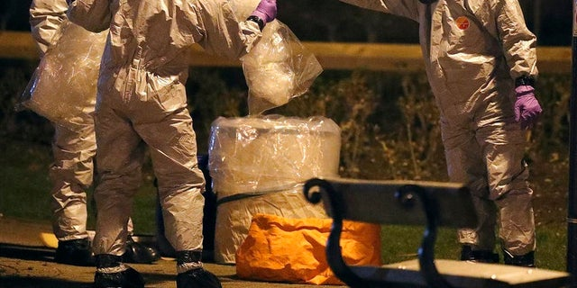 Soldiers in protective gear investigate the poisoning of a former Russian spy and his daughter in Britain.