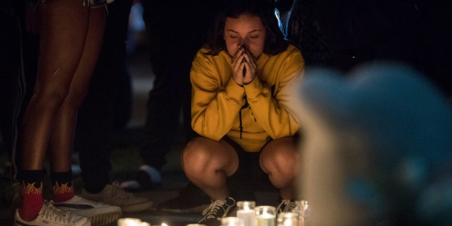 In this Tuesday, June 19, 2018 photo, fans and community members gather at the vigil for rap singer XXXTentacion in Deerfield Beach, Fla., near the site where the troubled rapper-singer was killed the day before.