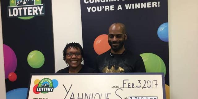 Yahnique, left, with her husband and their giant check.