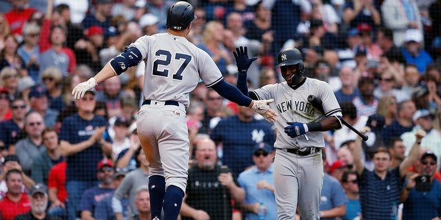 New York Yankees' Giancarlo Stanton (27) celebrates his solo home run with Adeiny Hechavarria during the seventh inning against the Boston Red Sox in Boston, Sept. 29, 2018.