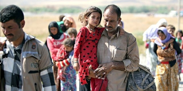 File photo: A displaced Yazidi Iraqi carries his daughter as they cross the Syrian border at Fishkhabour.