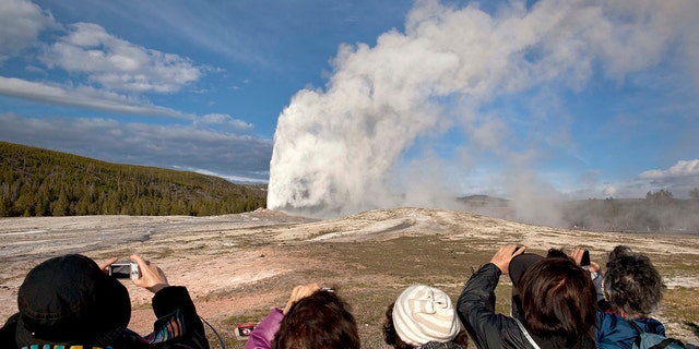 In this May 21, 2011, file photo, tourists photograph Old Faithful erupting on schedule late in the afternoon in Yellowstone National Park, Wyo.