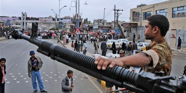 """May 25: A Yemeni army soldier stands guard at a checkpoint in Sanaa, Yemen. Yemen's embattled President Ali Abdullah Saleh issued messages of hard-line defiance Wednesday even as intense battles raged in the heart of the capital for a third day, saying he will not step down or allow the country to become a """"failed state."""" (AP)"""