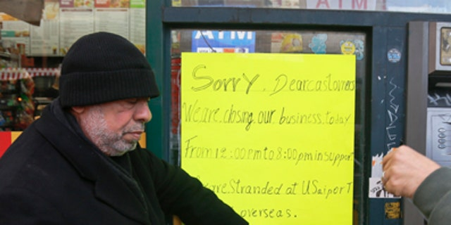 Zamood Zokari, left, and Ali Elazab, right, post a sign on a window of their family's deli in Manhattan.