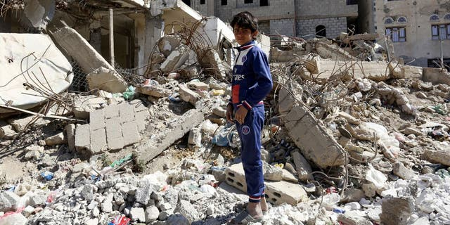 Sana'a. Ali, 13 years old, stands in the middle of destroyed buildings in his neighborhood.