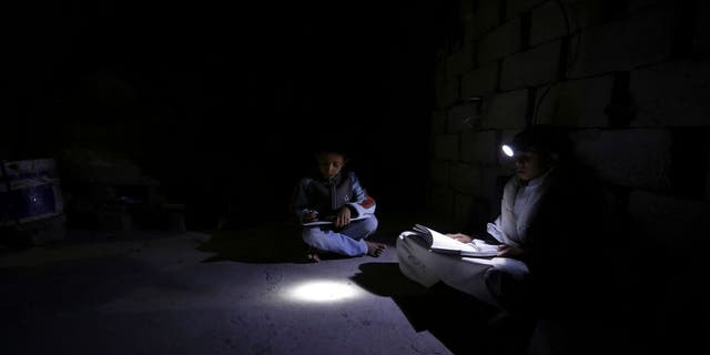 Sana'a. Intense darkness prevails over the neighborhood due to a severe shortage of electricity. Hisham, 14 years old, and Yazan, 8 years old, study in a room inside their home. E