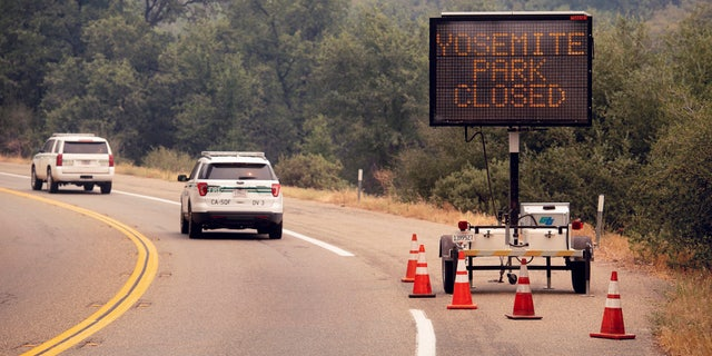 In this July 25, 2018 file photo, a sign on Highway 41 announces the closure of Yosemite National Park near Oakhurst, Calif.