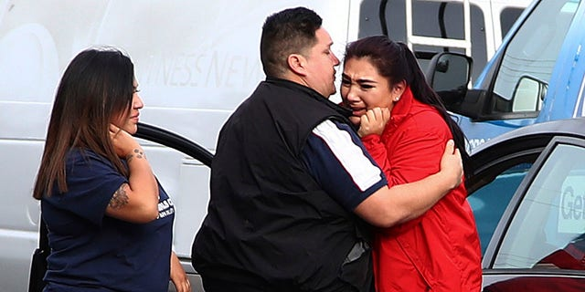 Fernando Juarez, 36, of Napa, center, embracing his 22-year-old sister Vanessa Flores, right, at the Veterans Home of California on Friday. Flores, who is a caregiver at the facility, exchanged texts with family while sheltering in place.