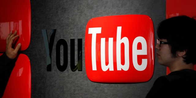 Feb. 14, 2013: Visitors stand in front of a logo of YouTube at the YouTube Space Tokyo, operated by Google, in Tokyo.