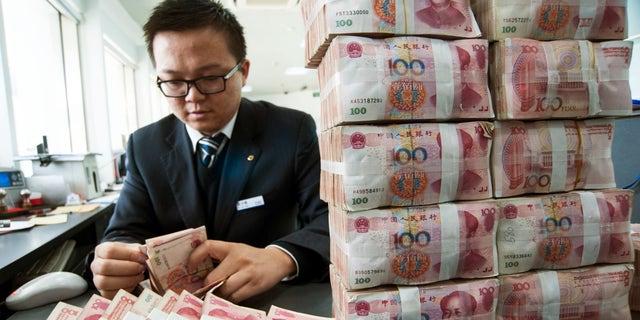 Dec. 2, 2014: A clerk counts Chinese 100 yuan banknotes at a branch of China Construction Bank in Nantong, Jiangsu province.