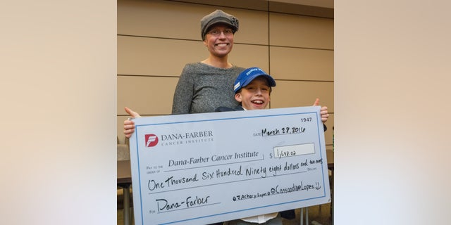 Zach Lopes and his mother, Christine, pose for a photo with the check Zach presented to the Dana-Farber Cancer Institute.