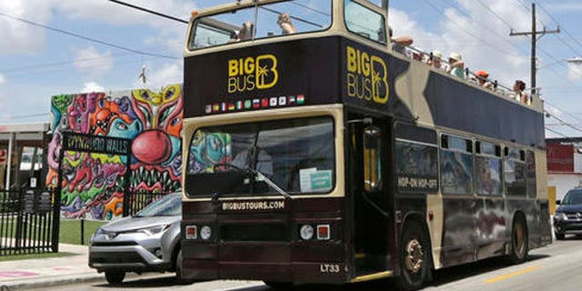A tour bus makes a stop in front of the Wynwood Walls, Friday, Aug. 5, 2016, in the Wynwood area of Miami. Thank goodness it's the slow season in Florida. At least that's what officials and representatives of the state's $82 billion tourism industry are thinking in the wake of news that 15 people were infected with Zika in one small, trendy neighborhood in Miami. (AP Photo/Alan Diaz)