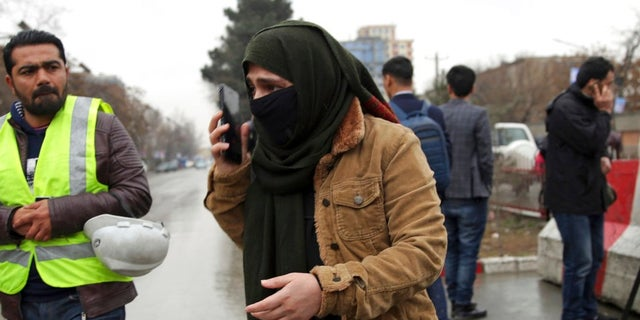 A woman talks to her phone as her relative was at the site of a suicide bombing in the diplomatic area of capital Kabul, Afghanistan