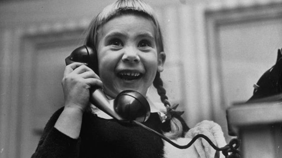 Photos of kids on the phone with Santa, 1947