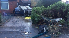 Car flips into driveway and catches fire as driver goes on the run