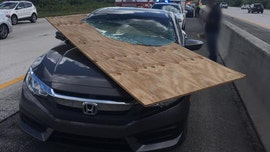Florida driver escapes injury after plywood impales car windshield