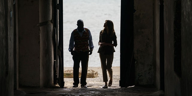 """First lady Melania Trump looks up as she walks through the """"Door Of No Return"""" with Cape Coast Castle museum educator Kwesi Essel-Blankson as she visits Cape Coast Castle in Cape Coast, Ghana, Wednesday, Oct. 3, 2018. The first lady is visiting Africa on her first solo international trip. (AP Photo/Carolyn Kaster)"""