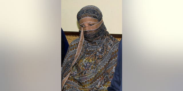 FILE 2010: Asia Bibi, a Pakistani Christian woman, listens to officials at a prison in Sheikhupura near Lahore.