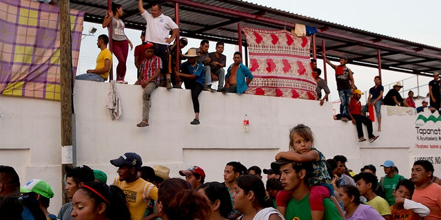Migrants wait in lines to receive donated food as others look on in Tapanatepec, Mexico.