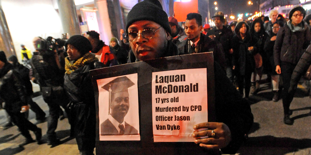 FILE - In this Nov. 24, 2015 file photo, a man holds a sign with a photo of Laquan McDonald on it, during a protest of the police shooting 17-year-old McDonald, in Chicago. The city of Chicago is watching closely for word of a verdict in the case of Chicago police Officer Jason Van Dyke charged with murder in the 2014 shooting of McDonald. The Chicago Police Department has canceled days off and put officers on 12-hour shifts. (AP Photo/Paul Beaty, File)