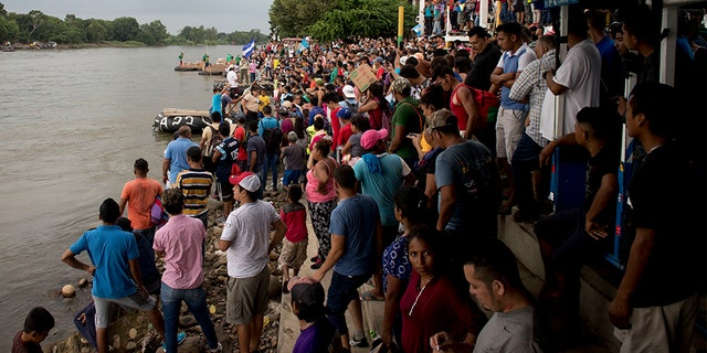 Hundreds of Honduran migrants stand at the shore of the Suchiate river on the border between Guatemala and Mexico, in Tecun Uman, Guatemala.