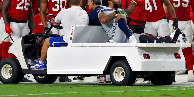 Seattle Seahawks defensive back Earl Thomas is greeted by Arizona Cardinals players as he leaves the field after breaking his leg during the second half of an NFL football game.