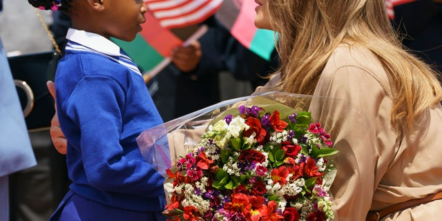 First lady Melania Trump is greeted by a flower girl as she arrives at Lilongwe International Airport, in Lumbadzi, Malawi. (AP Photo/Carolyn Kaster)