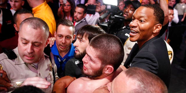 FILE: Khabib Nurmagomedov, bottom center, is held back outside of the cage after fighting Conor McGregor in a lightweight title mixed martial arts bout at UFC 229.