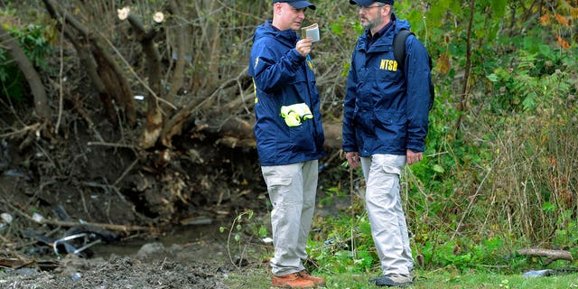 Members of the National Transportation Safety Board work at the scene of yesterday's fatal crash, in Schoharie, N.Y.