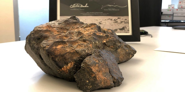 A 12-pound lunar meteorite discovered in Northwest Africa in 2017 rests on a table, in Amherst, N.H.