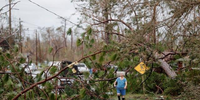 Carol Ralph walks through downed trees blocking her heavily damaged neighborhood just after Hurricane Michael passed through in Panama City.