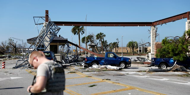 A soldier stands guard at the damaged entrance to Tyndall Air Force Base.