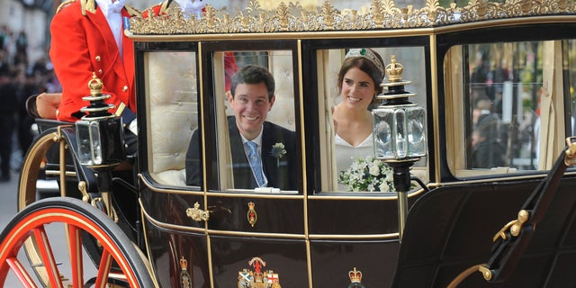 Princess Eugenie of York, right, and Jack Brooksbank travel from St George's Chapel to Windsor Castle after their wedding at St George's Chapel, Windsor Castle, near London, England, Friday, Oct 12, 2018. (AP Photo/Rui Vieira)