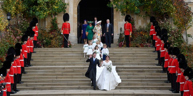 Britain's Princess Eugenie and Jack Brooksbank leave St George's Chapel after their wedding at Windsor Castle, near London, England, Friday Oct. 12, 2018. (Toby Melville, Pool via AP)