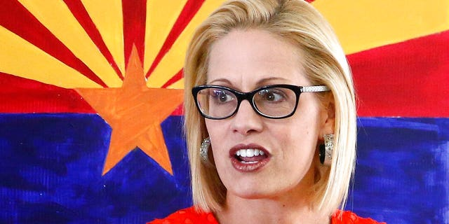 Then-U.S. Rep. Kyrsten Sinema, D-Ariz., talks to campaign volunteers in Phoenix in August 2018 during her U.S. Senate campaign. (Associated Press)