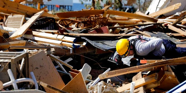 A member of a South Florida urban search and rescue team sifts through a debris pile for survivors of hurricane Michael in Mexico Beach, Fla., Sunday, Oct. 14, 2018.
