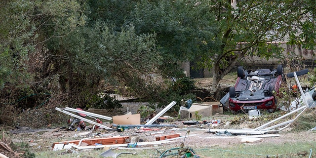 A car and debris are pictured after floods in the town of Villegailhenc, southern France, Monday, Oct.15, 2018. Flash floods tore through towns in southwest France, turning streams into raging torrents that authorities said killed several people and seriously injured at least five others. (AP Photo/Fred Lancelot)