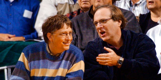 In this March 11, 2003 file photo, Microsoft Chairman Bill Gates, left, chats with Portland Trail Blazers owner and former business partner Paul Allen during a game between the Trail Blazers and Seattle SuperSonics in Seattle.