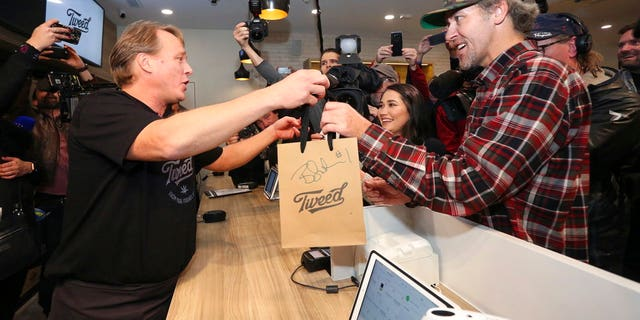 Canopy Growth CEO Bruce Linton, left to right, passes a bag with the first legal cannabis for recreation use sold in Canada to Nikki Rose and Ian Power at the Tweed shop on Water Street in St. John's N.L. at 12:01 am NDT on Wednesday Oct. 17, 2018